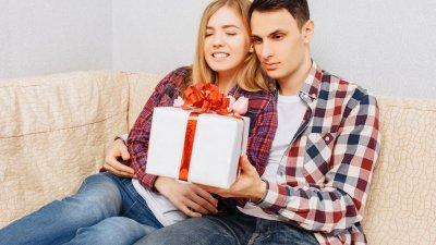 Homem entregando presente para mulher, ambos estão sentados em sofá