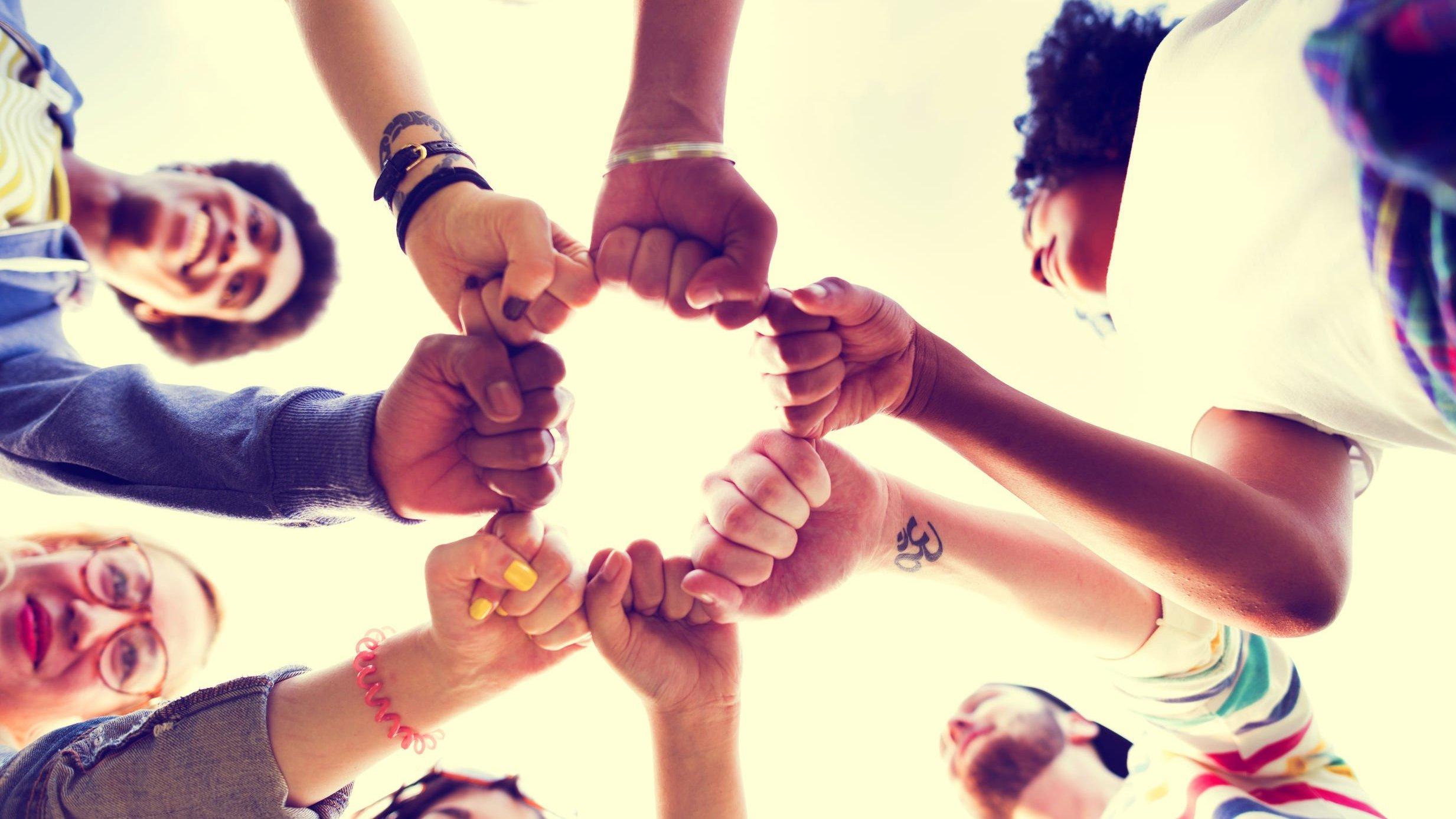 Amigos formando roda e dando as mãos.