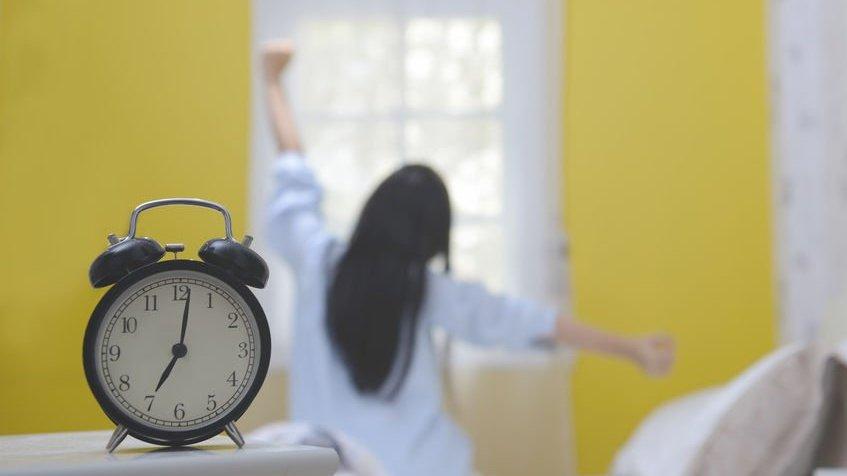 Mulher sentada na cama se espreguiçando ao lado de um relógio, que marca as 7 horas