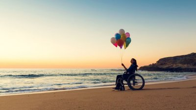 Pessoa de cadeira de rodas na praia segurando balões