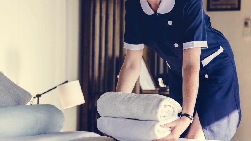 Doméstica com toalhas dobradas