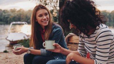Duas mulheres conversando e segurando uma caneca