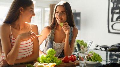 Duas mulheres brancas sentadas num banco comendo vegetais.