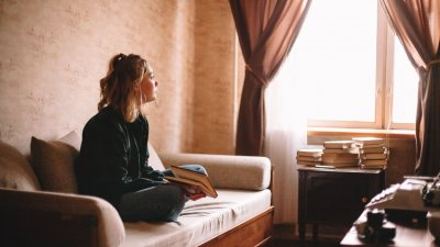 Menina adolescente sentada no sofá de sua casa, com um livro em mãos, olhando pela janela