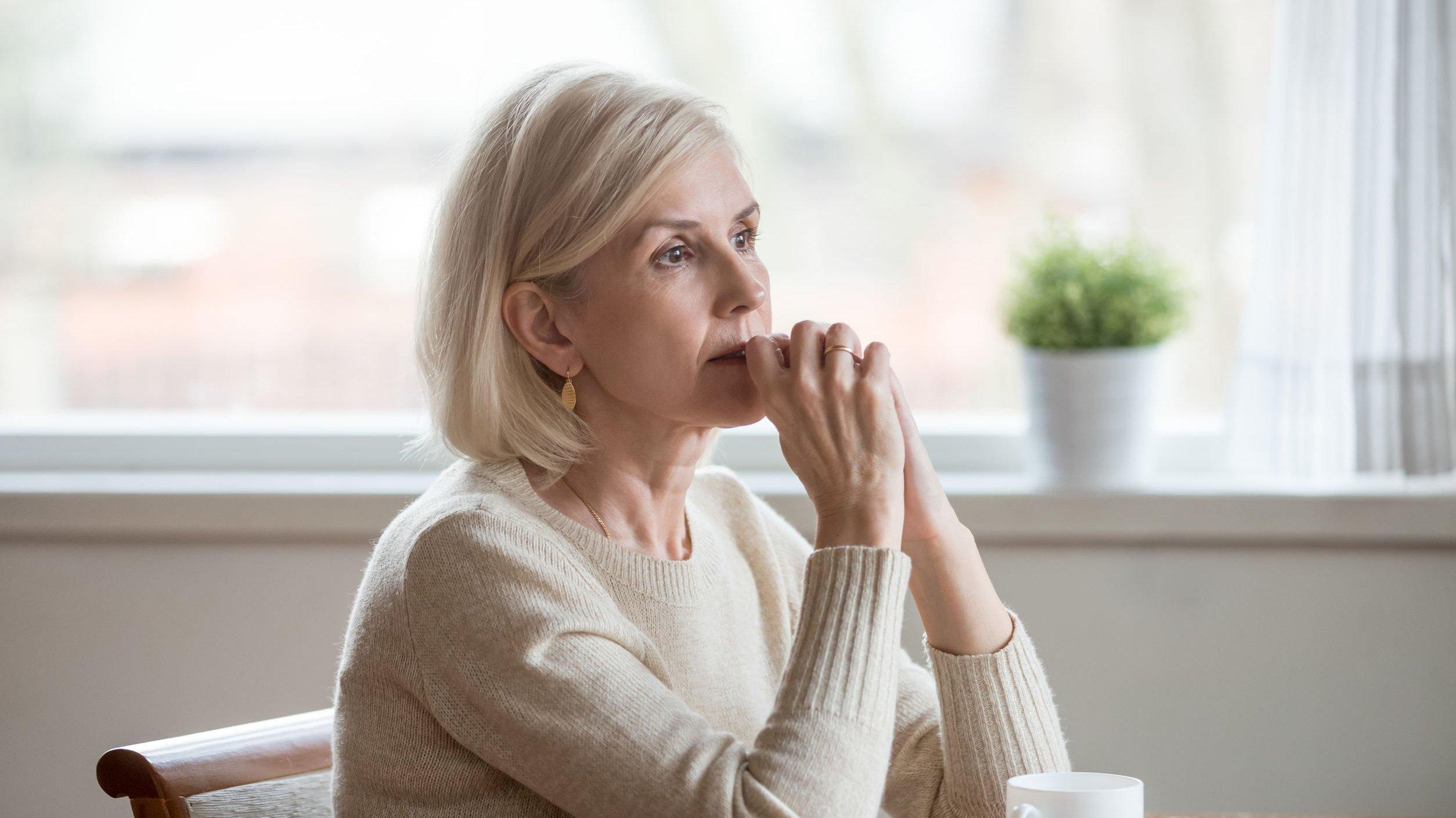 Mulher sentada, expressando estar pensando.