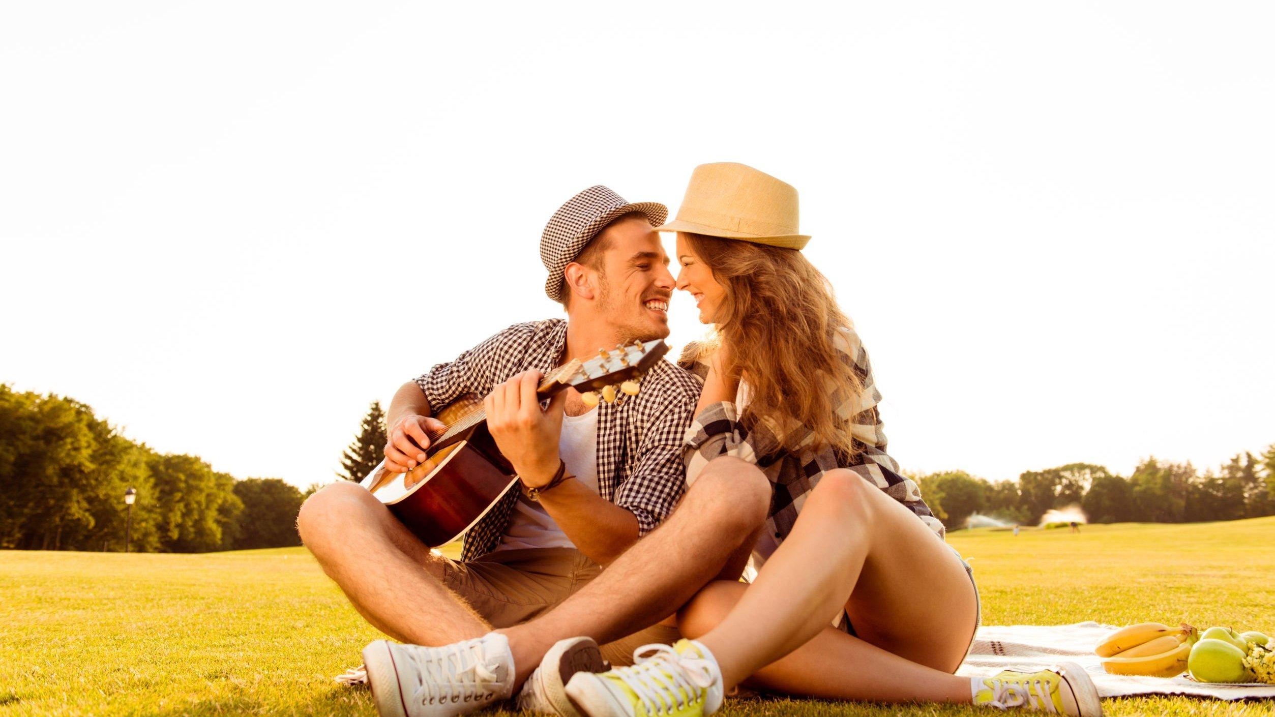 Casal sentado em campo. Homem segurando violão.