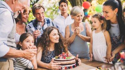 Pessoas comemorando aniversário em volta de menina com bolo