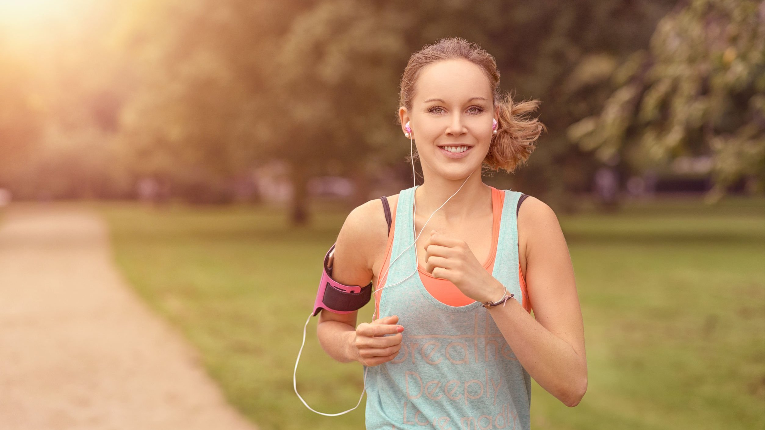 Mulher correndo e sorrindo.