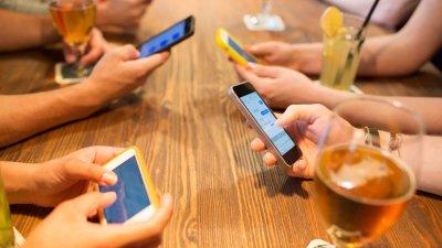 Pares de mãos apoiadas numa mesa de madeira segurando celulares com copos ao lado.