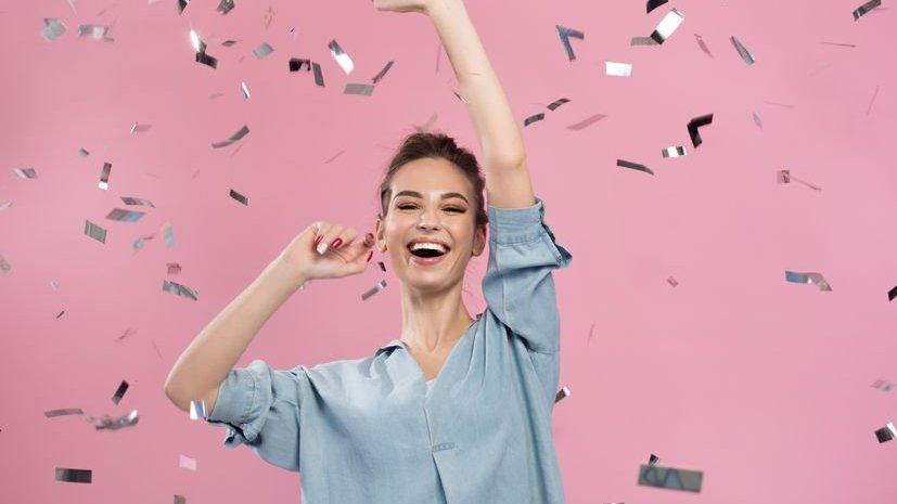 Mulher rindo com as mãos para cima em meio a confetes caindo