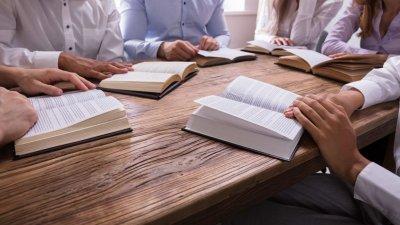 Grupo de pessoas em uma mesa lendo suas Bíblias