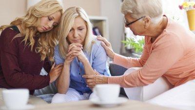 Mulheres brancas e loiras com expressões tristes prestando apoio.