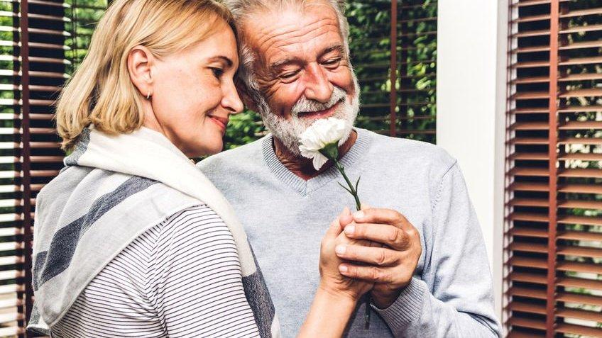 Homem e mulher segurando ramo de flor