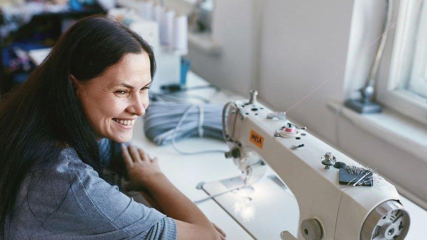 Mulher sorrindo sentada em mesa com máquina de costura em frente