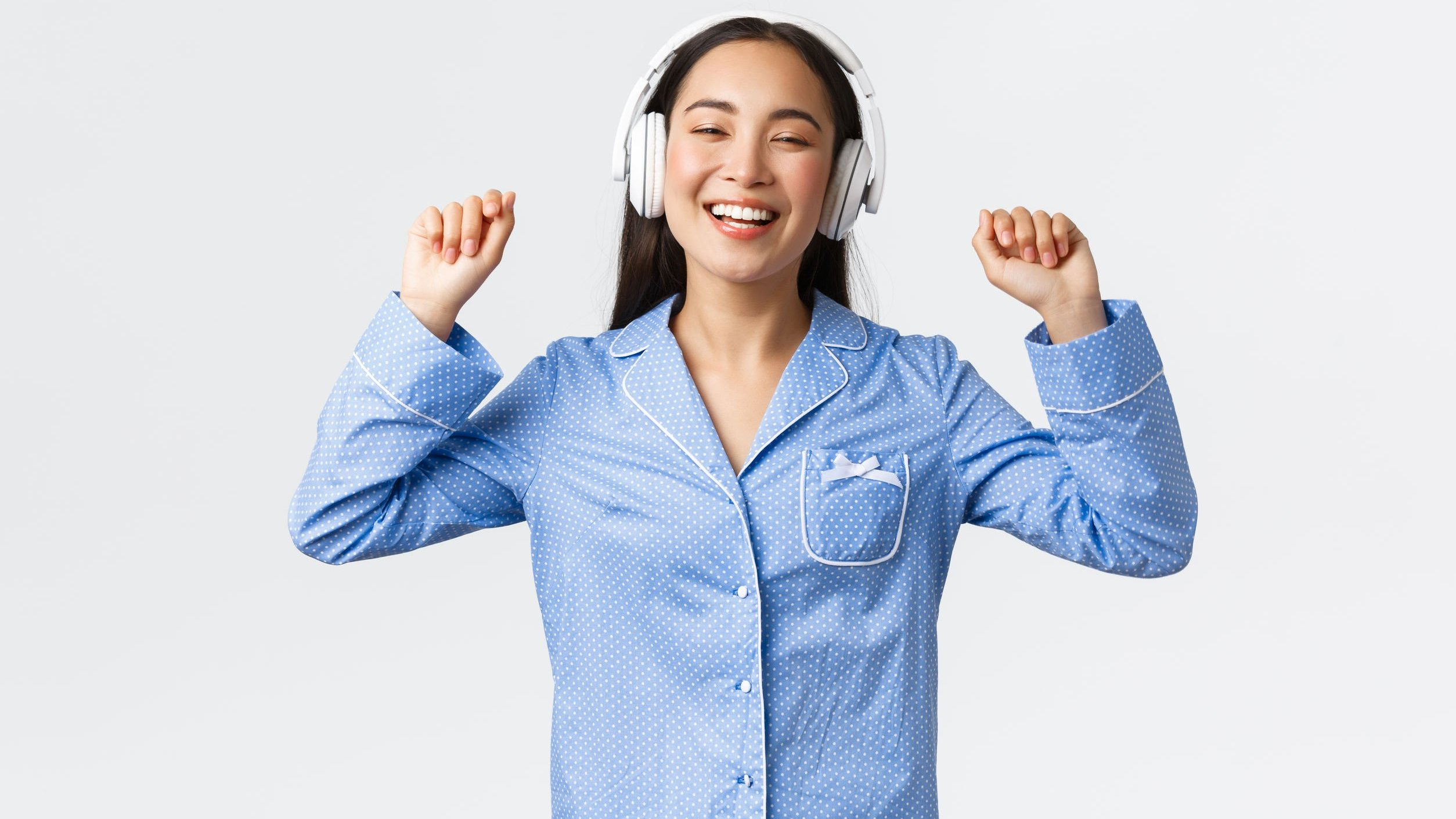 Mulher sorrindo de pijama e fones de ouvido