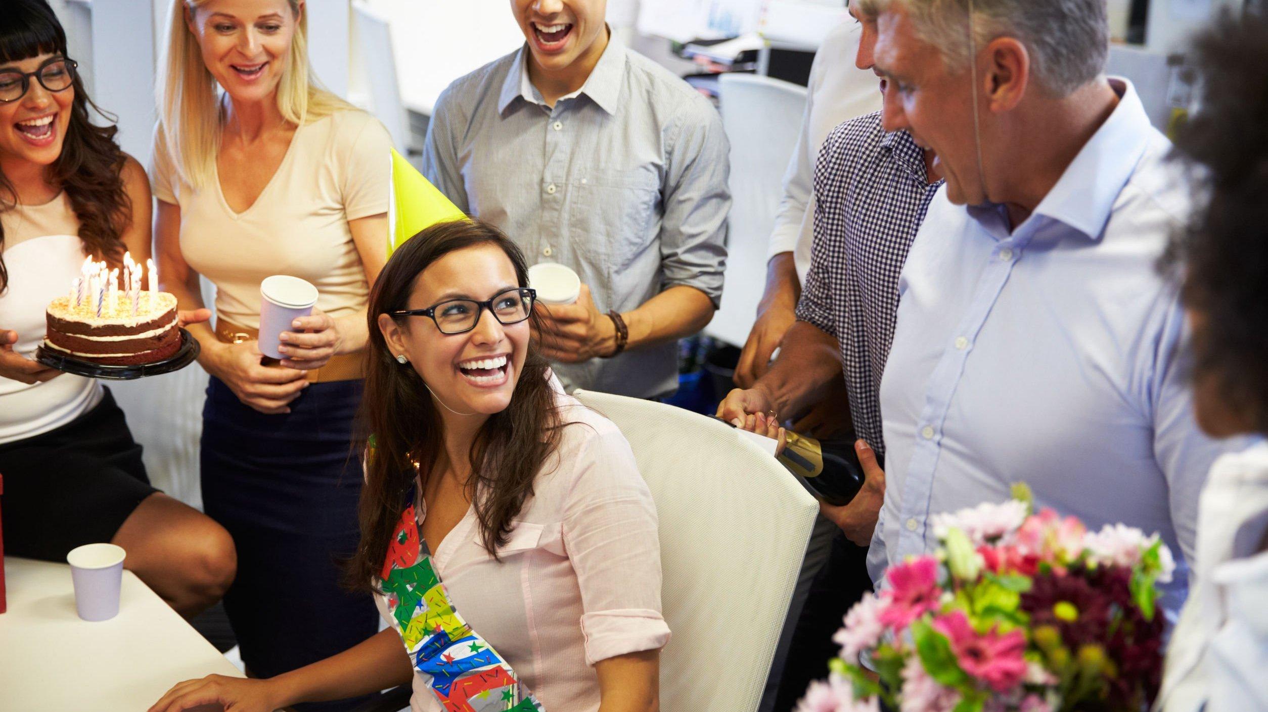 Pessoas reunidas comemorando aniversário em escritório