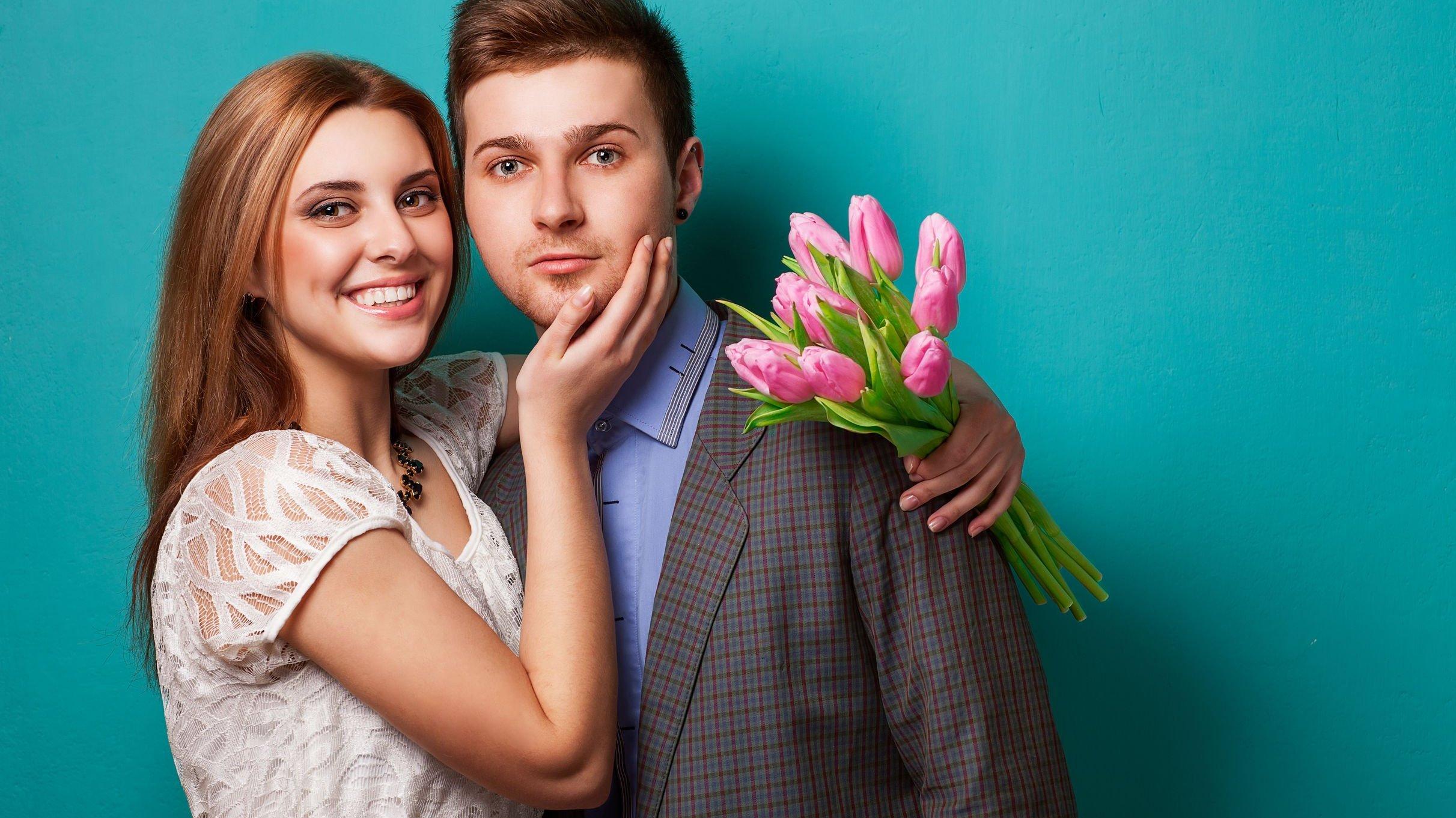Mulher sorrindo e segurando flores,abraçando homem.