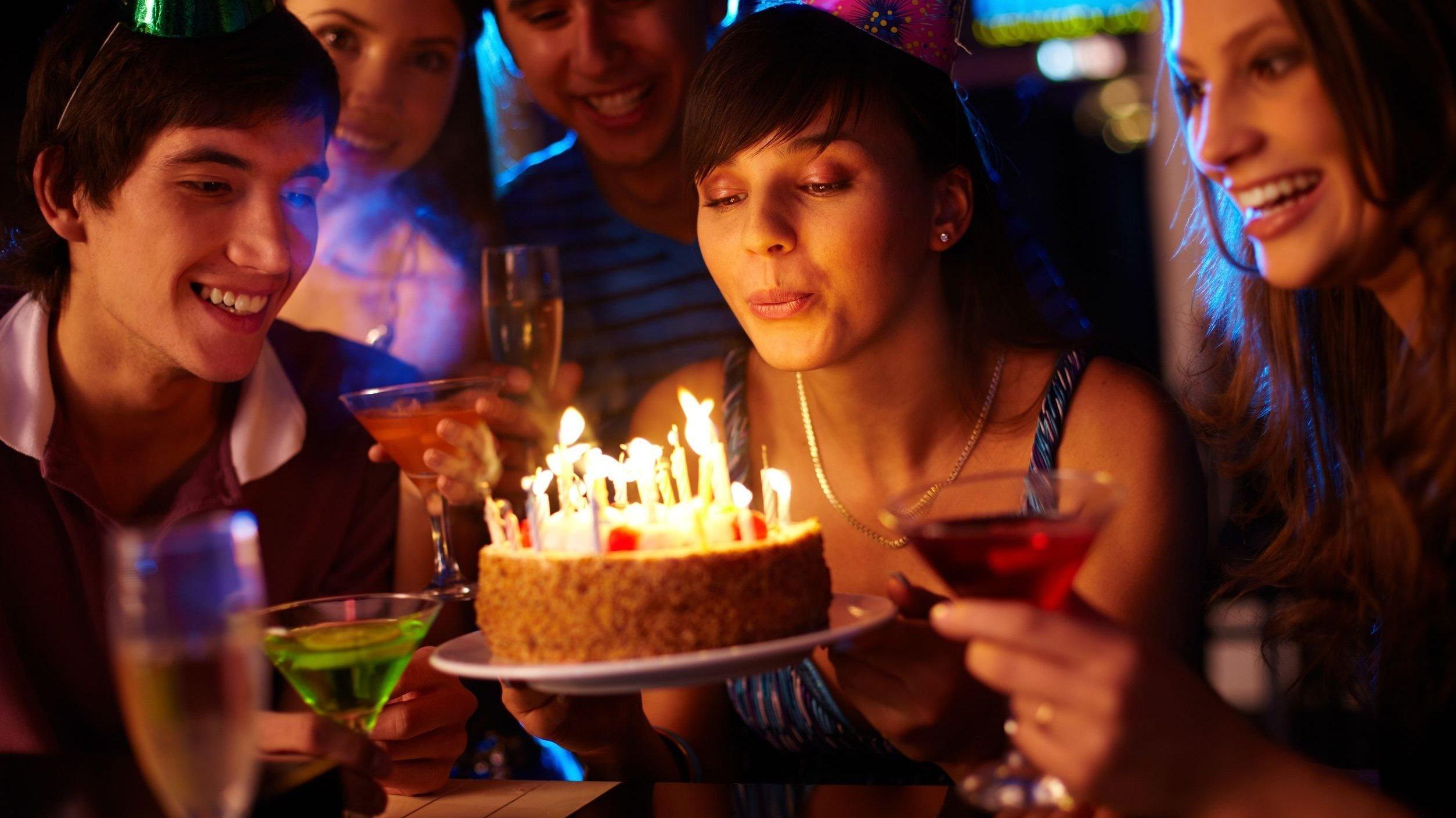 Pessoas cantando parabéns. Mulher segurando bolo e assoprando velhinha acessa.