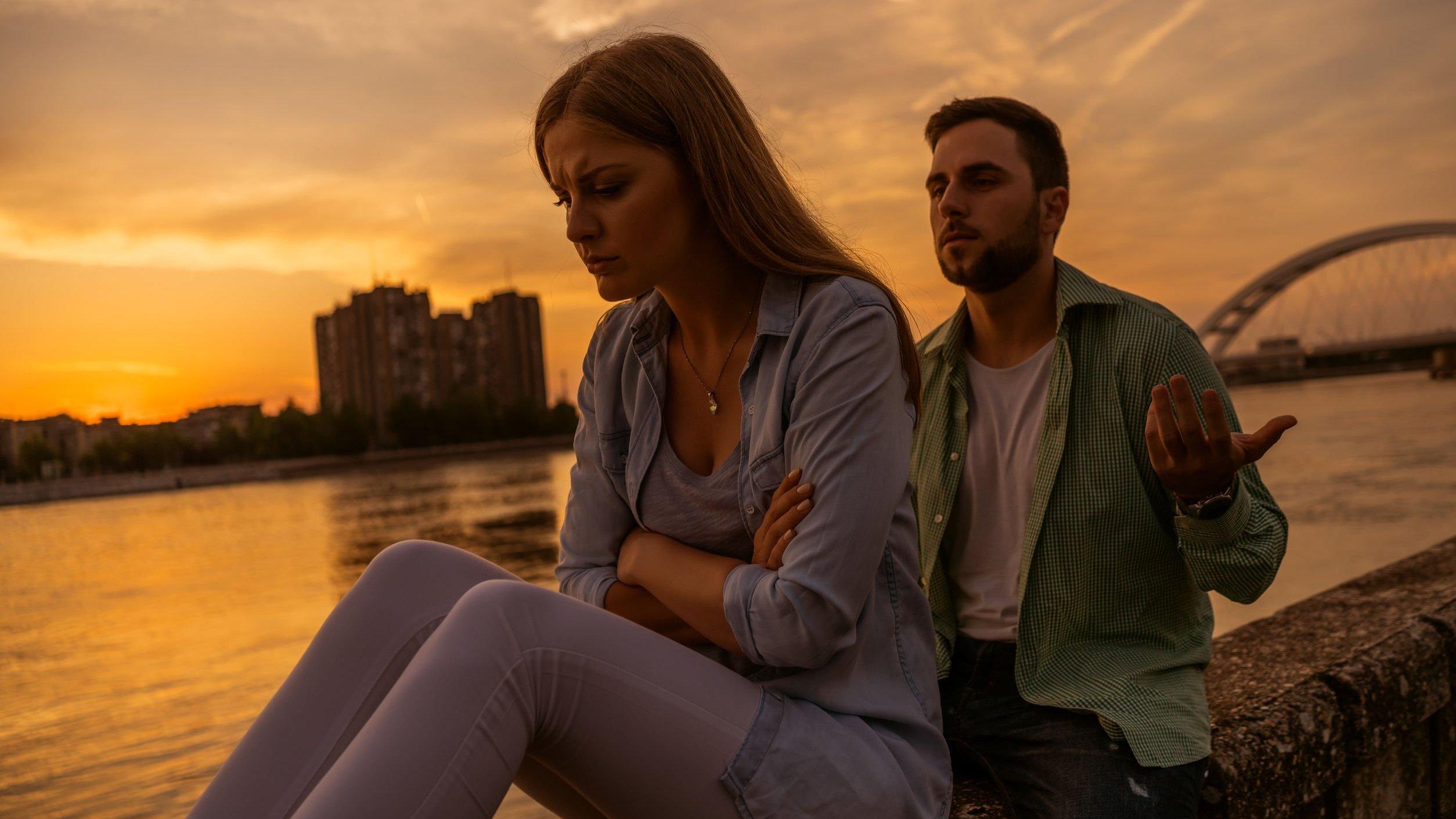 Homem e mulher brancos sentados numa mureta ao lado de um rio. Mulher com braços cruzados e expressão triste, homem com braços abertos e expressão de súplica.