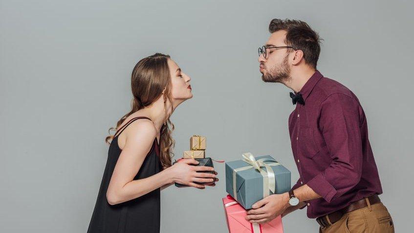 Homem e mulher segurando presentes e fazendo bico de beijo