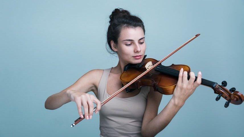 Uma jovem com um violino sobre o fundo azul