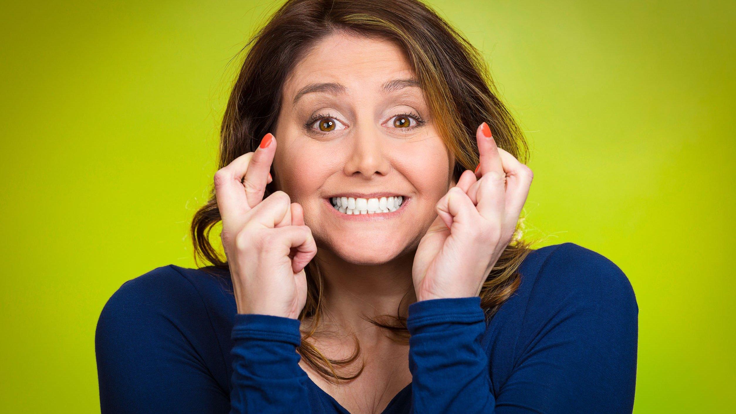 Mulher sorrindo com os dedos cruzados.