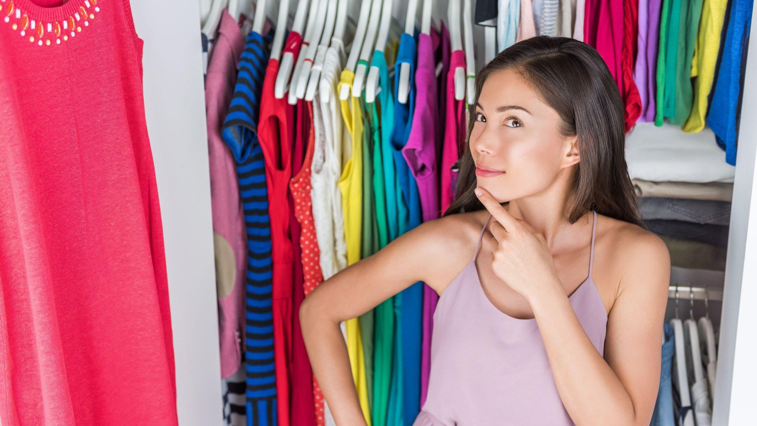 Mulher com a mão sobre o queixo, olhando para guarda roupas organizado.
