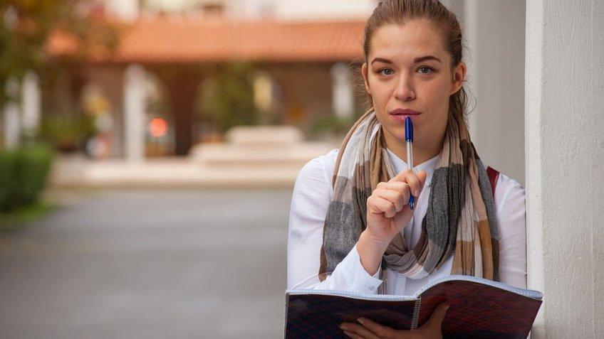 Mulher com caneta posicionada nos lábios e segurando caderno