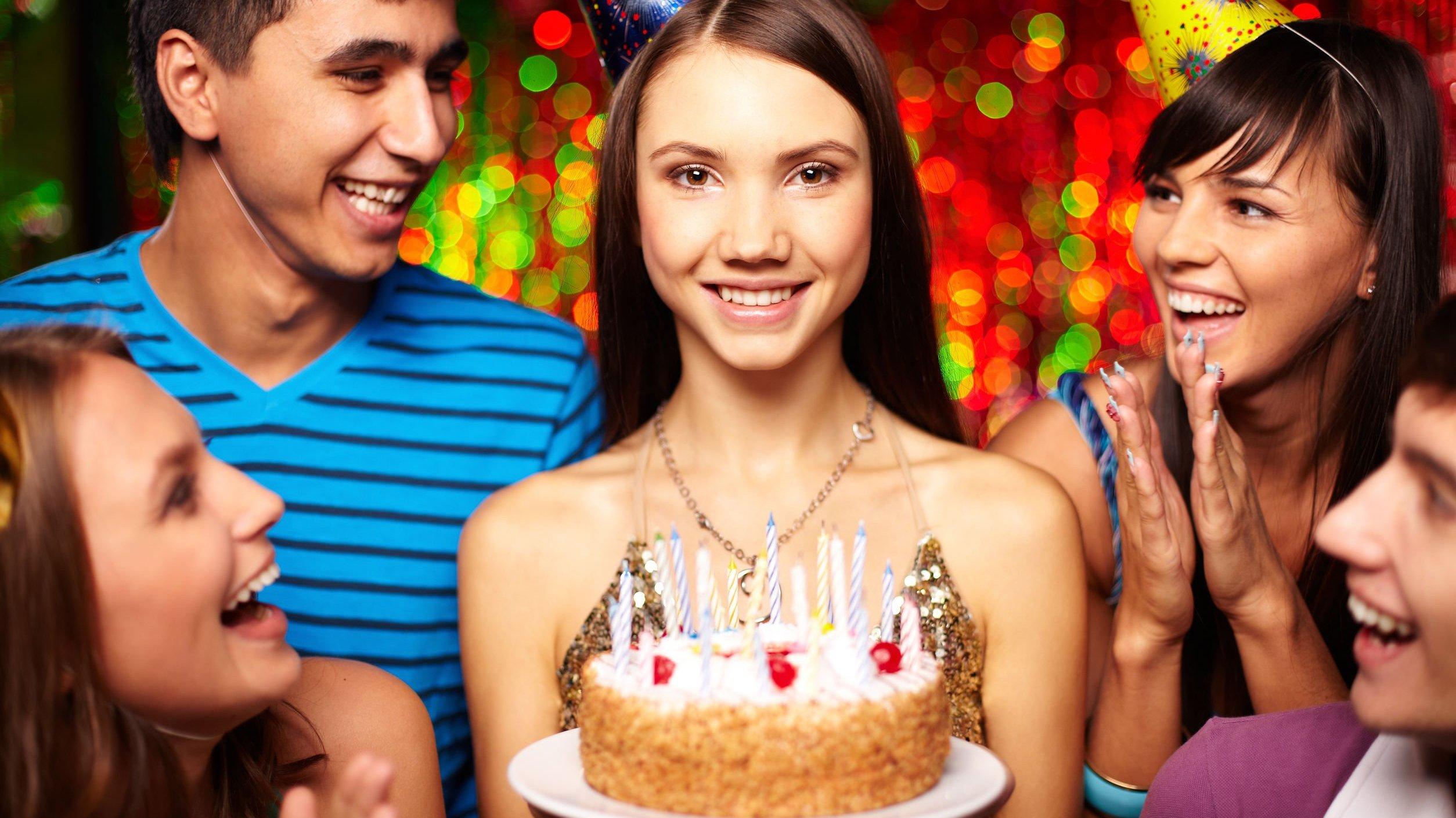 Pessoas comemorando aniversário e mulher sorrindo, segurando bolo.