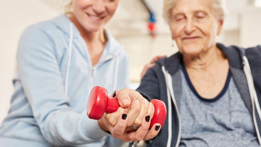 Terapeuta ajudando idosa a fazer exercício