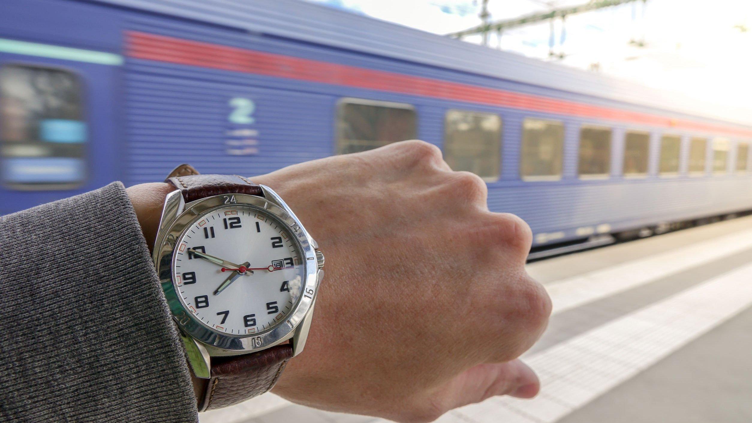 Braço com relógio e trem passando ao fundo.