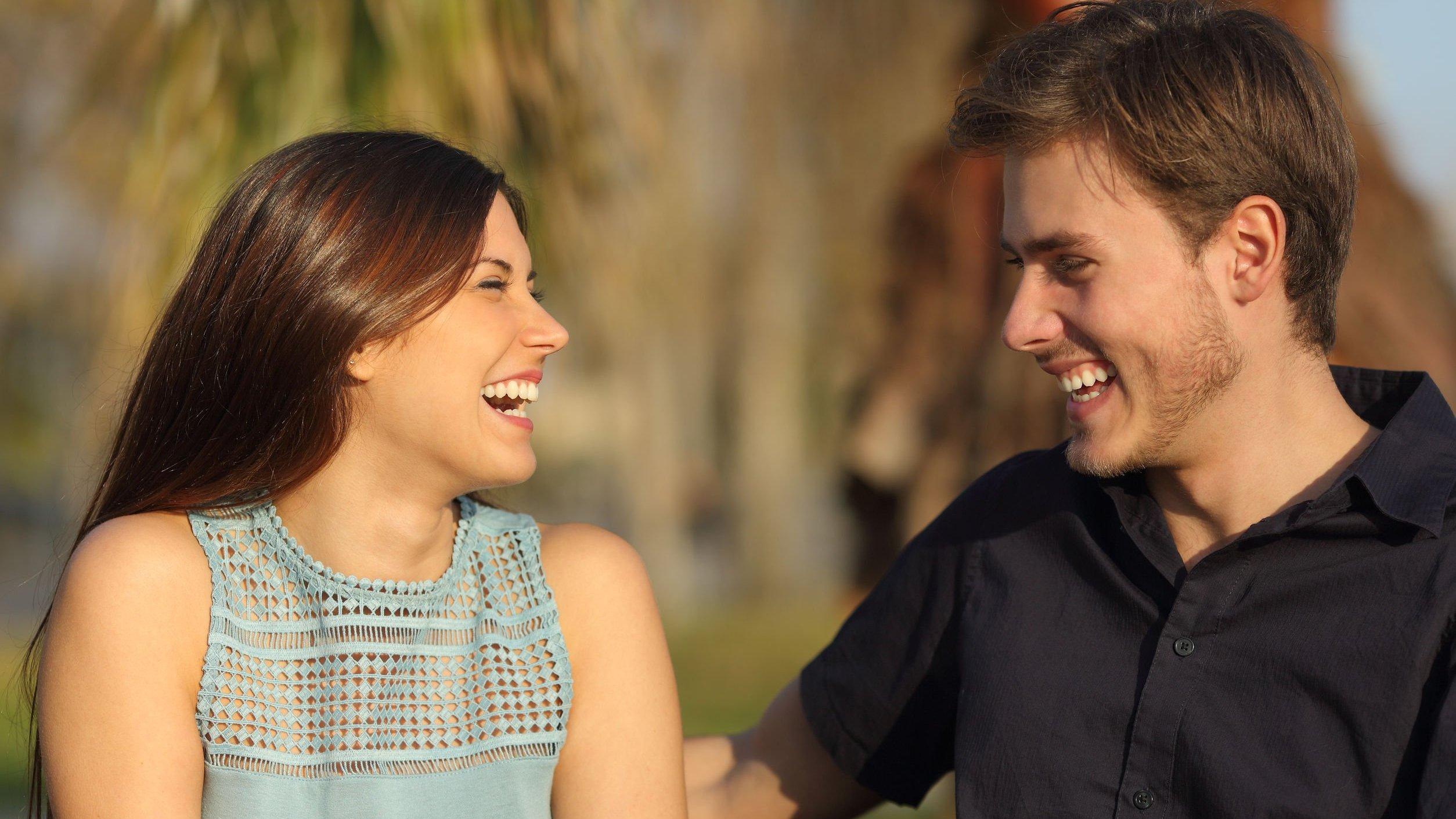Homem e mulher sorrindo conversando.