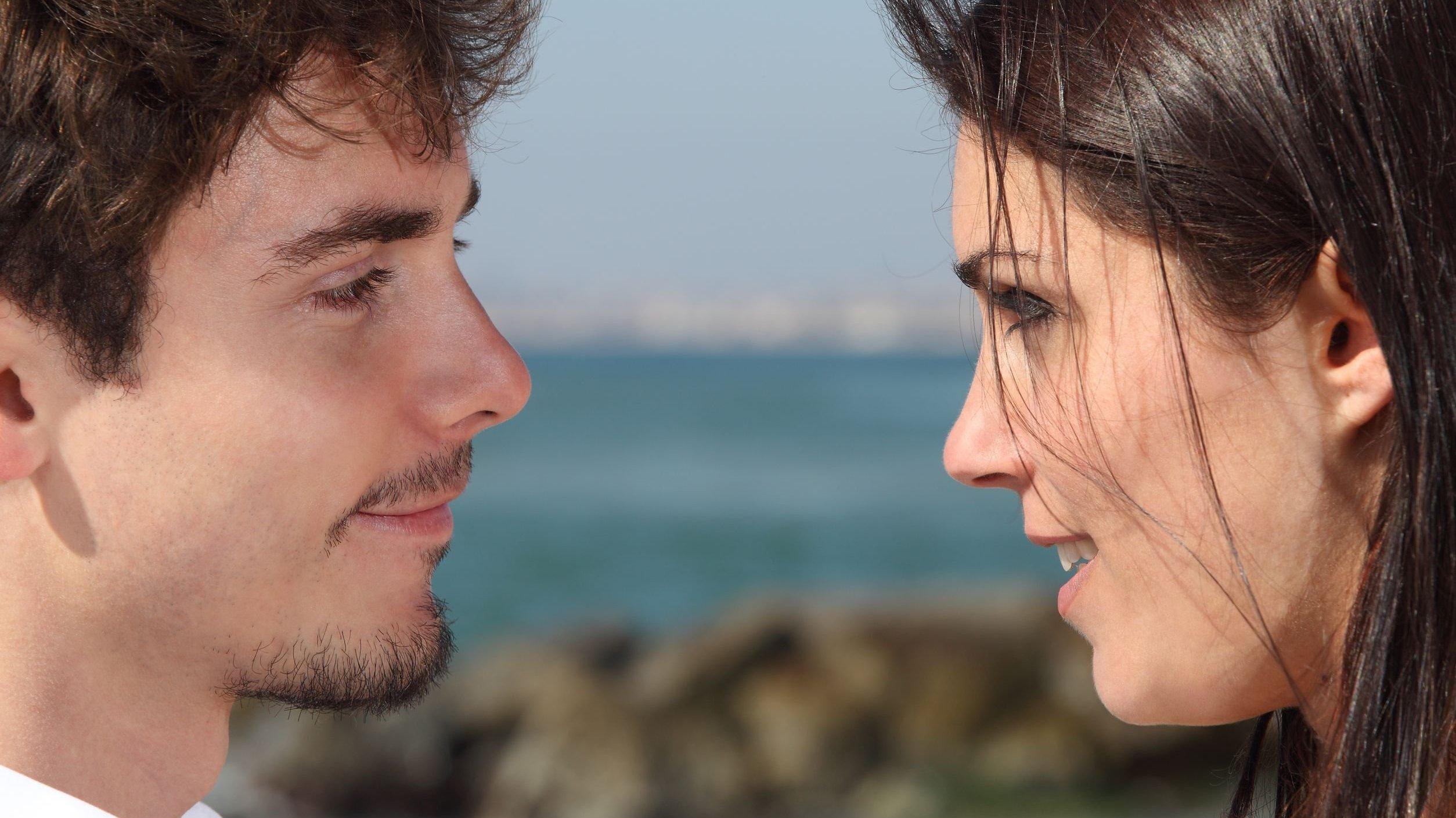 Homem e mulher se olhando e sorrindo.