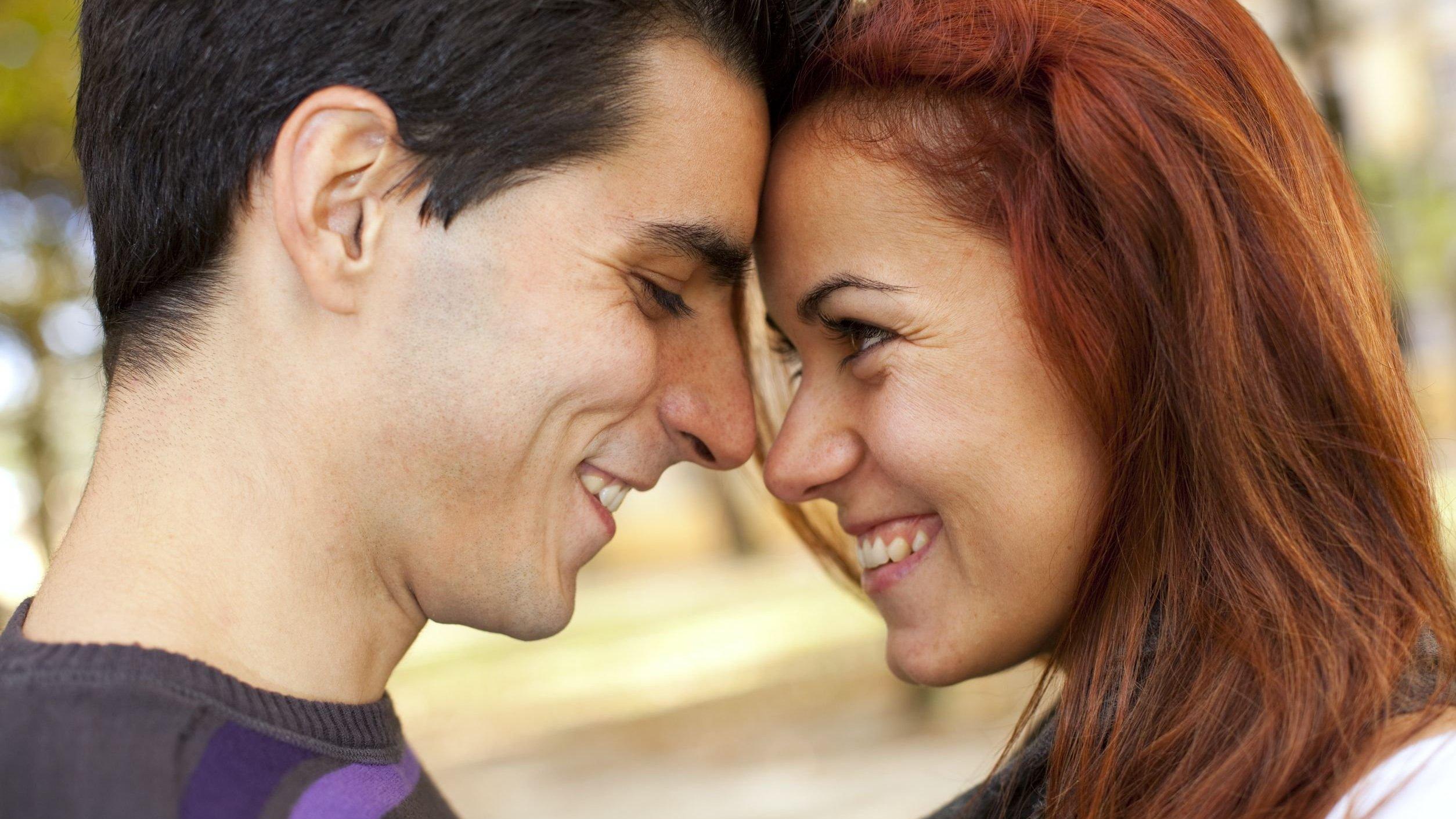 Casal se olhando e sorrindo em parque.