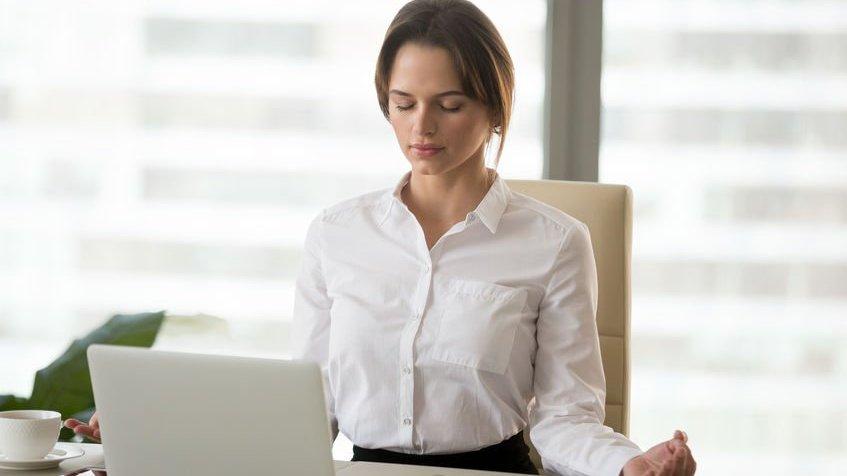 Mulher de olhos fechados meditando em frente ao computador