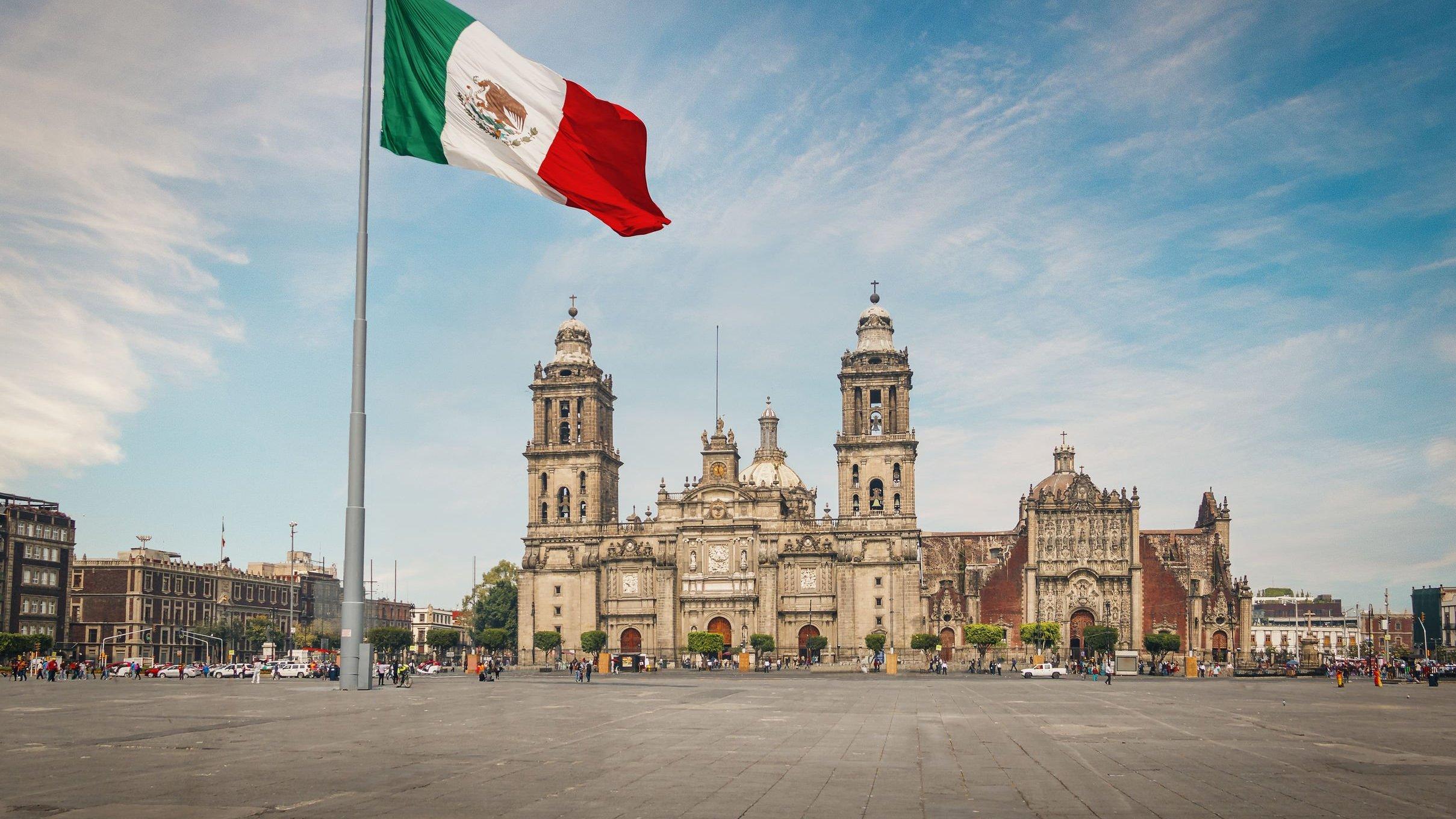 Cidade e bandeira do México ao fundo.