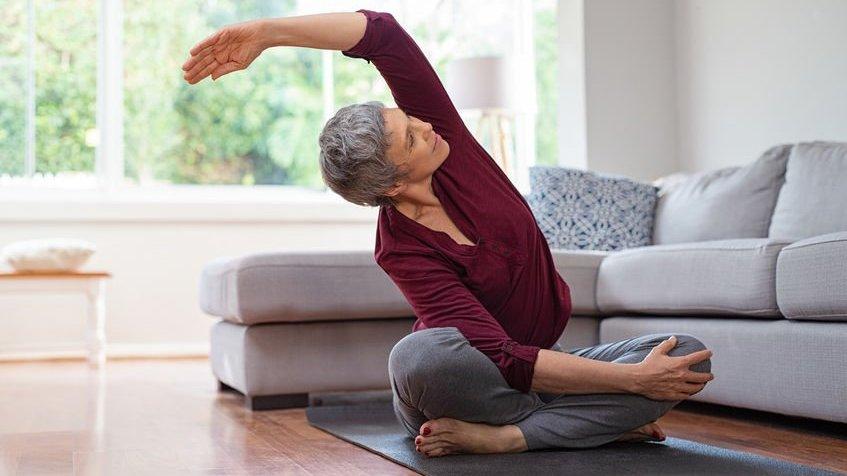Mulher praticando Yoga em sala de estar