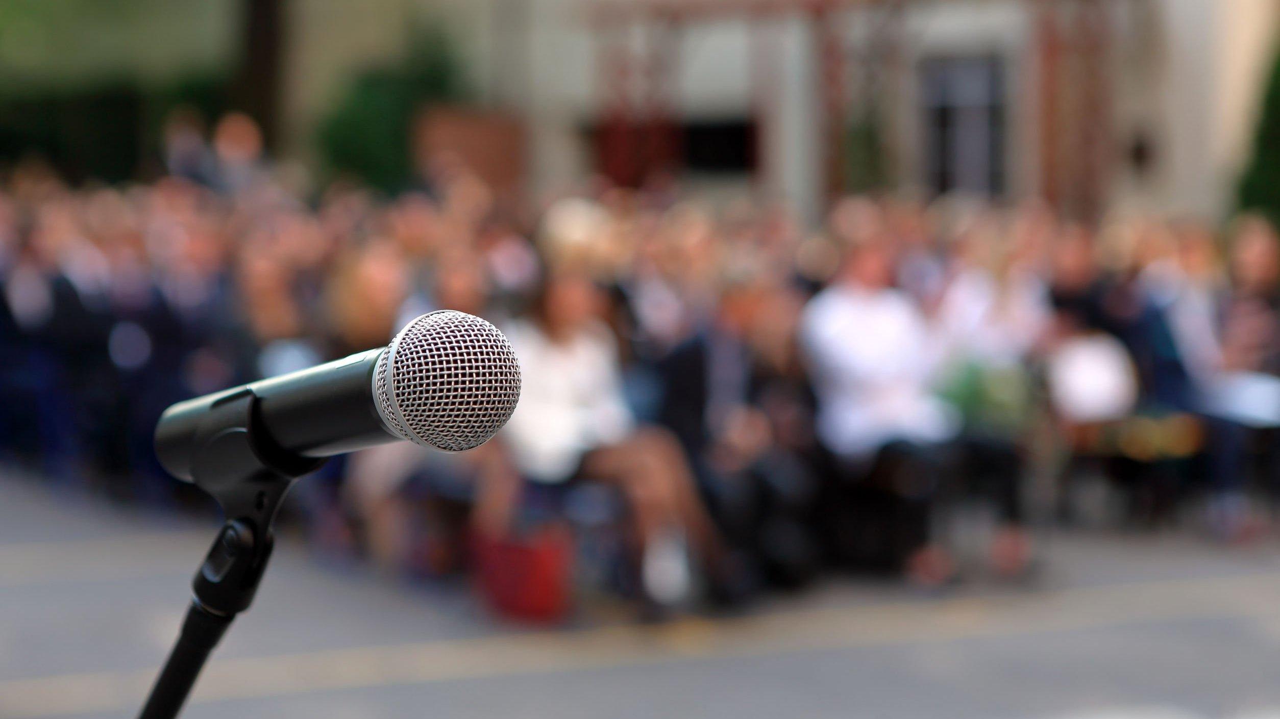 Microfone e plateia ao fundo, aguardando discurso.
