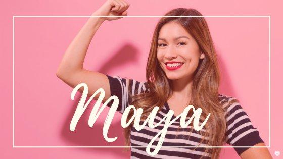 Mulher sorrindo fazendo sinal de força com o braço, com o nome Maya escrito em branco