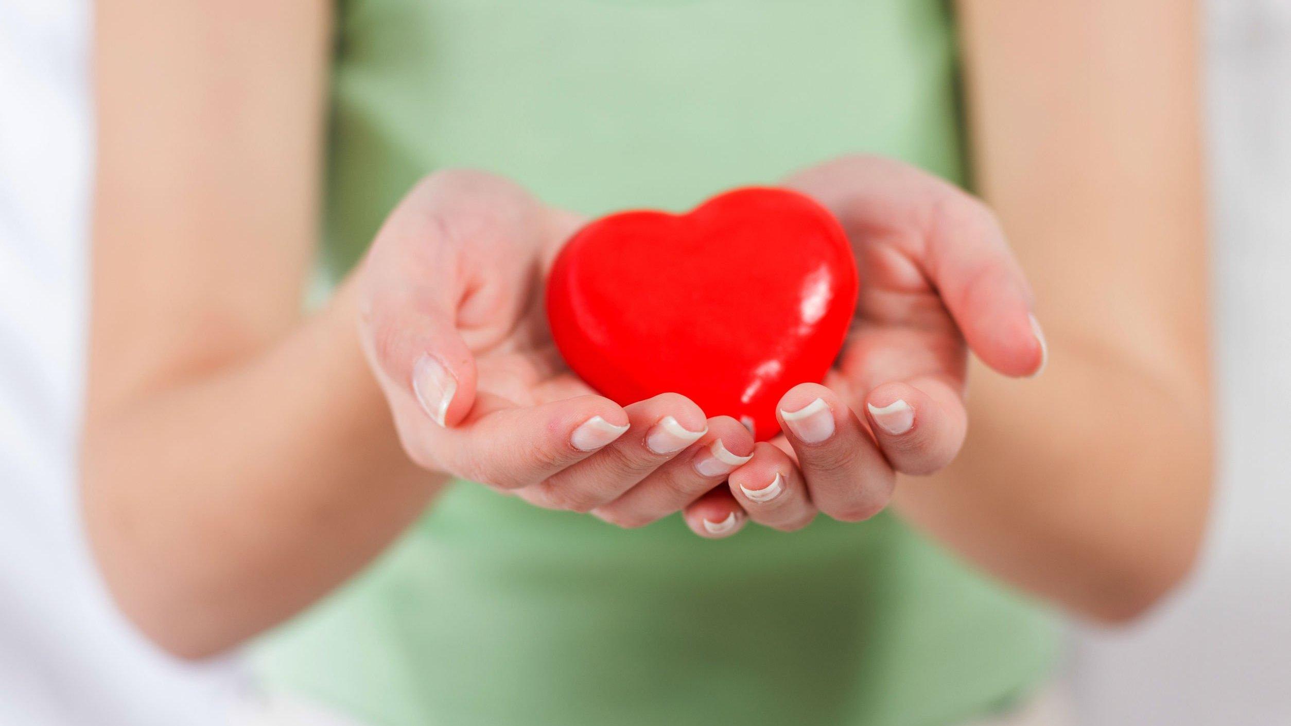 Mãos de mulher segurando coração.