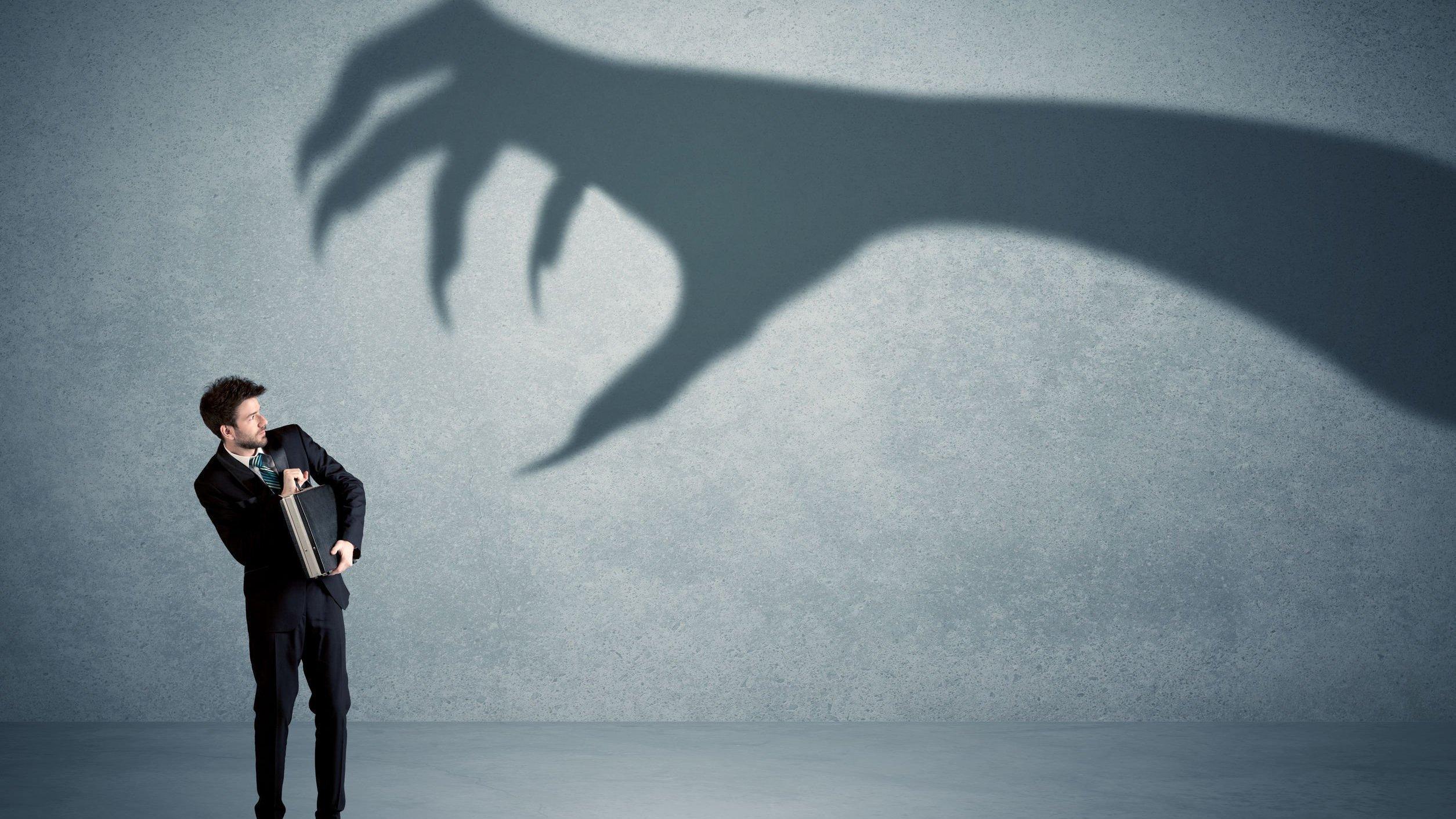 Homem com medo, olhando para sombra de mão em parede.