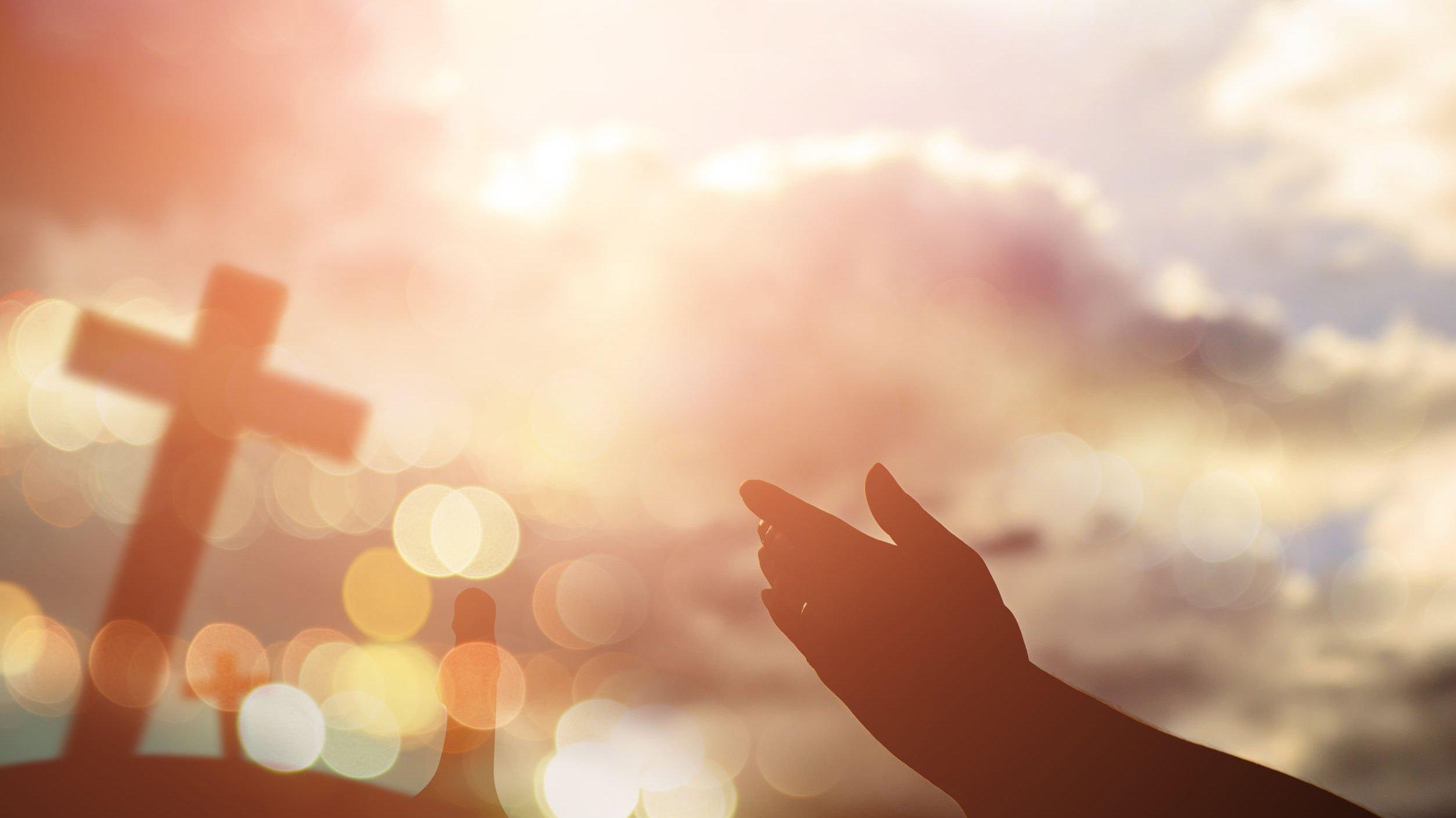 Mãos de pessoa orando, apontando para cruz.
