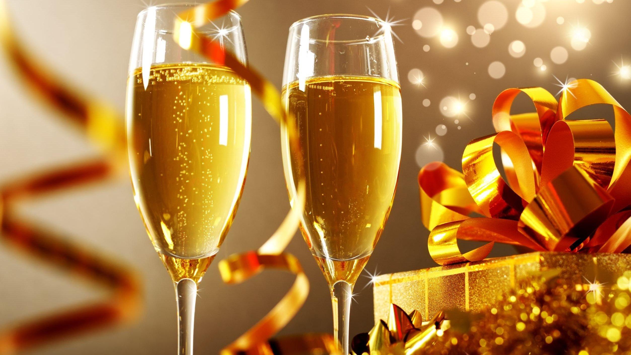 Duas taças de champanhe ao lado de uma caixa de presente