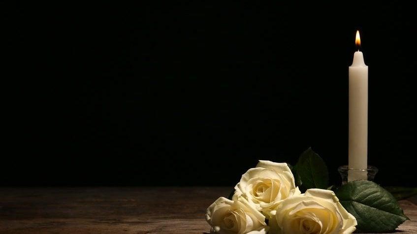 Vela acesa e flor ao lado