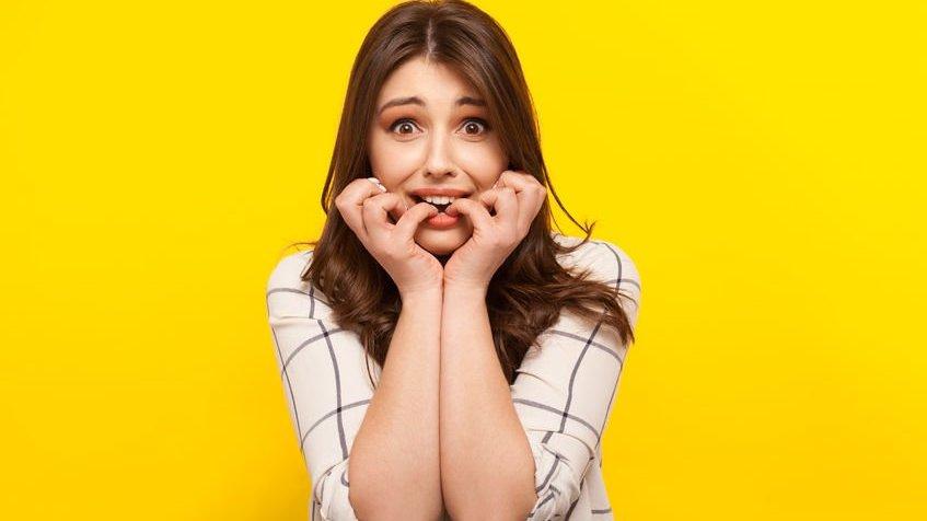 Menina  mordendo os dedos com o fundo amarelo