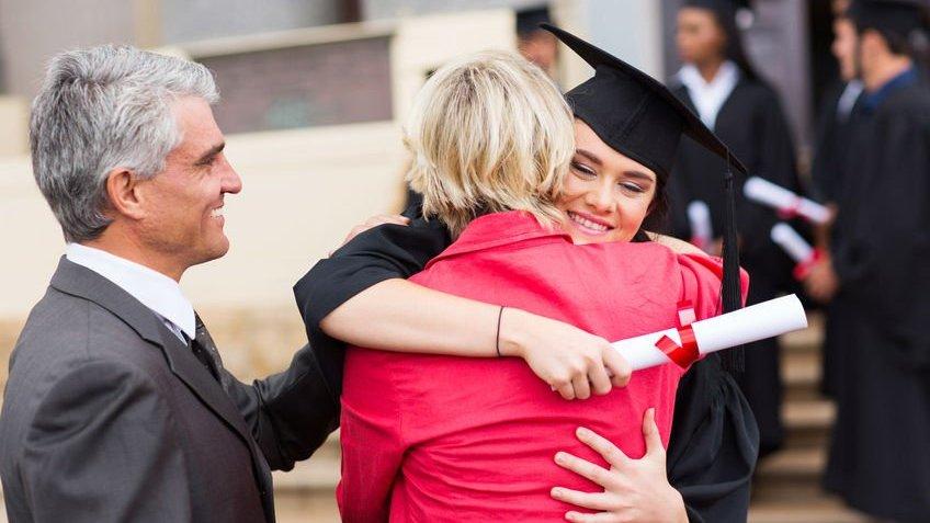 Formanda abraçando mulher e homem ao lado