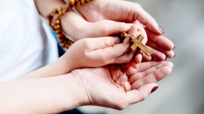 Mãos de mãe e filho segurando um rosário