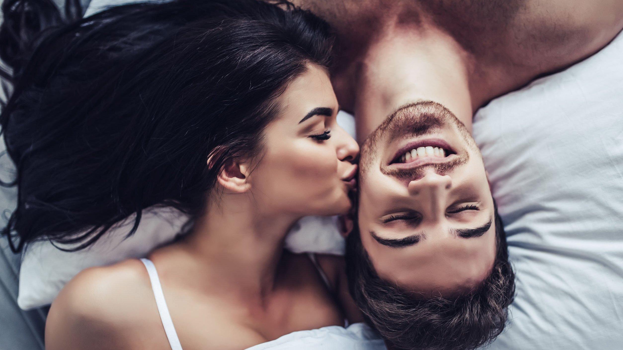 Mulher beija o rosto de um homem, os dois estão deitados em uma cama.
