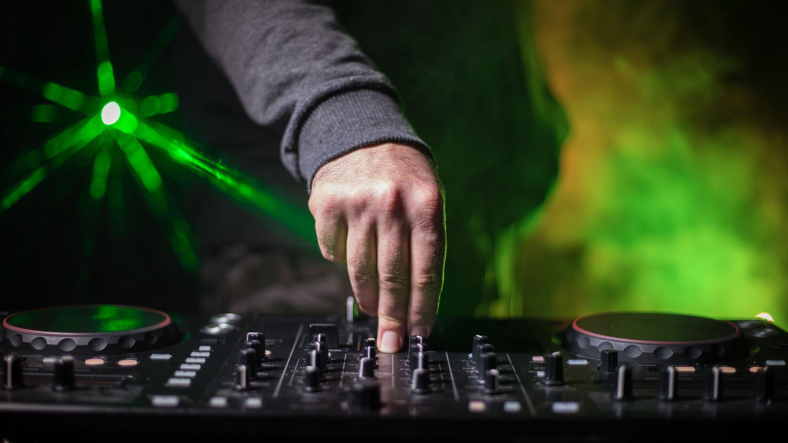 Mão de DJ em mesa de som.
