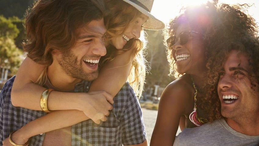 Uma mulher branca está sorrindo para uma mulher negra, enquanto está nas costas de um homem branco alegre. Já a mulher negra está nas costas de um homem negro sorridente , enquanto sorri de volta para a mulher branca